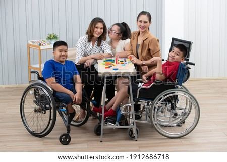Group of special students in classroom, a down syndrome girl, two handicapped boys and cute Asian teacher playing toy and game together. Stock photo ©