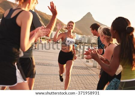 Group of spectators cheering runners just before the finish line. Female runner finishing the race with her team applauding her efforts.