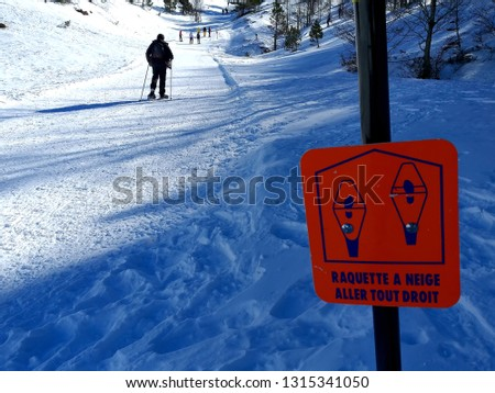 GROUP OF SPORT PEOPLE CLIMBING A MOUNTAIN PLENTY OF SNOW WITH RACKETS OF SNOW IN A CLEAR SUNNY DAY OF WINTER. AT FIRST AN ORANGE SIGNAL WARNING THAT IS A PATH FOR WALKING WITH RACKETS OF SNOW.