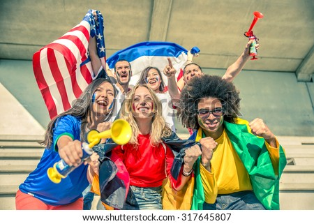 Group of sport supporters at stadium - Fans of diverse nations screaming to support their teams - Multi-ethnic people having fun and celebrating on tribune at a sport event  stock photo
