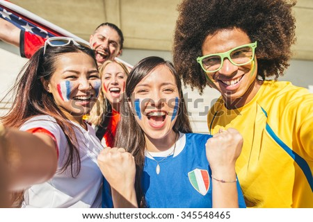 Group of sport supporters at stadium taking selfie - Fans of diverse nations screaming to support their teams - Multi-ethnic people having fun and celebrating on tribune at a sport event  stock photo