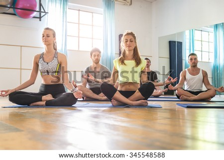 Group of sportive people doing yoga in a fitness gym - Sport group stretching after a work out
