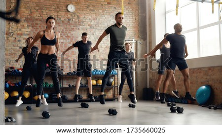 Group of sportive people jumping, warming up before having workout with dumbbells at industrial gym. Group training concept. Horizontal shot Stok fotoğraf ©