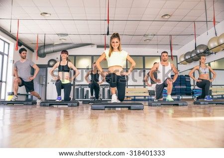 Group of sportive people training with step in fitness club - Aerobics class in a gym, coach showing legs exercise