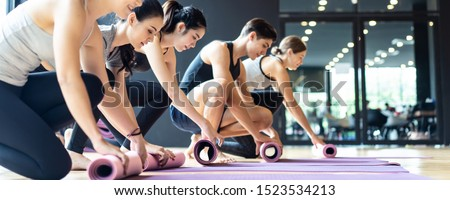 Group of sporty diversity people rolling the yoga mat after training yoga workout in studio room at gym fitness club. They have a good body shape and fit due to exercise and training yoga.
