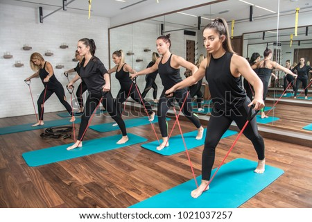 Group of sporty girls exercising with a resistance band in fitness studio. Foto stock ©