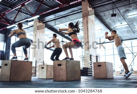 Group of sporty muscular people are working out in gym. Cross fit training. Jumping on a box together. #1043284768