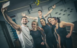 Group of sporty people in sportswear taking selfie photo at gym.