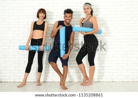 Group of sporty people with yoga mats near white brick wall #1135208861