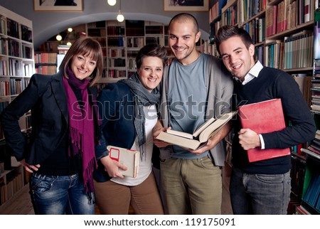 Group of students at a library smiling and holding books