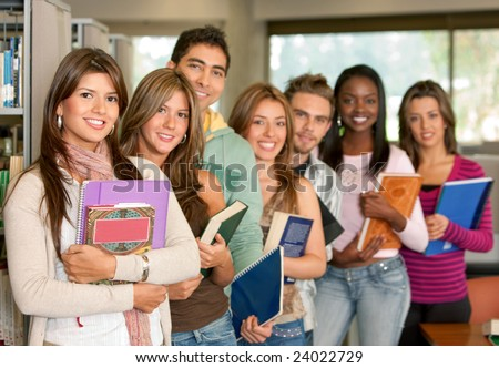 Group of students at a library smiling and holding some notebooks