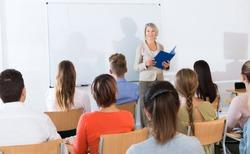 Group of students attentively listening to lecture of female teacher in classroom