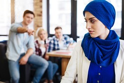 Group of students humiliating young muslim woman