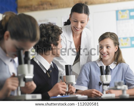 Group of students in discussion with teacher in laboratory