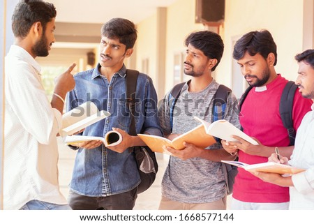 group of students listening to senior student to clear doubts - young intelligent man explaining to his classmates by looking into books at college - Education, Learning Student, People concept.