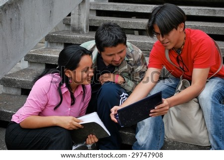 Group of students looking at a laptop - stock photo