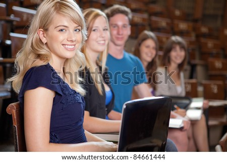 Group of students looking at camera in a university lecture hall