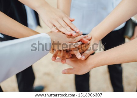 Group of students or businessman hands together joining for teamwork, community,  togetherness and business collaboration concept.