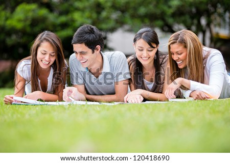Group of students outdoors studying and looking happy