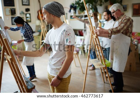 Group of students painting at art lessons