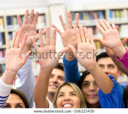 Group of students raising their hands to participate in class