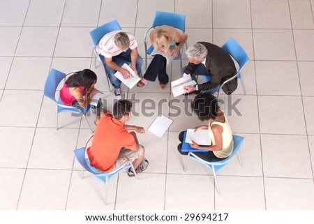 Group of students sitting down and studying with lecturer