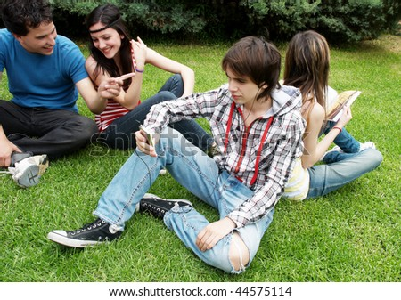 Group of students sitting in park on a grass #44575114