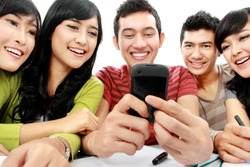 Group of students smiling looking at cellphone together