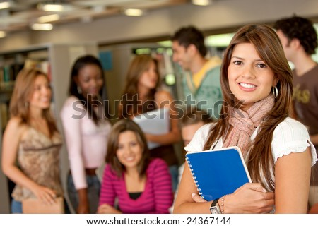 Group of students standing at the library smiling