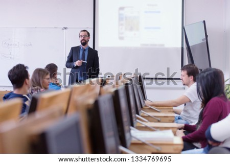 Group of students study with professor in modern school classroom. Male professor explain to students and interact with them, helping a students during class.