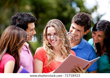 Group of students talking and holding notebooks outdoors