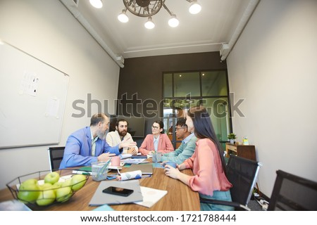 Group of stylish office workers sitting together in modern office board room doing brainstorming, copy space