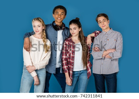 group of stylish teenagers standing together isolated on blue #742311841