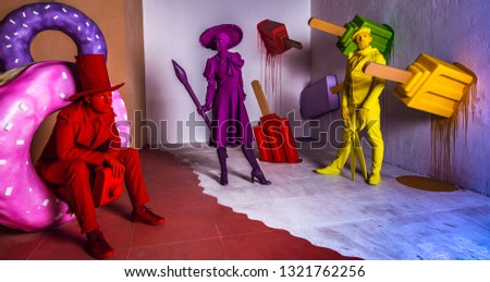 Group of stylized fantasy actors in scenic make-up and bright colored background.