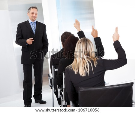 Group of successful business people at the lecture asking questions
