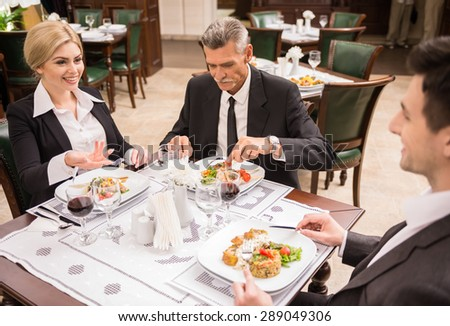 Group of successful business people discussing contract during business lunch.