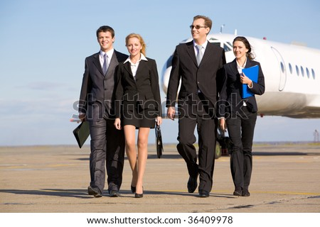 Group of successful people walking on the background of the airplane