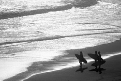 Group of surfers carrying surf boards standing at the shore of a beach and looking at the sea.