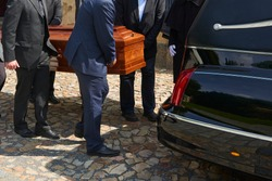 Group of survivors puts a coffin inside a hearse