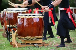 Group of Taiko drummers drumming on Japanese Drums together.