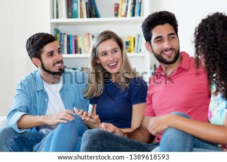 Group of talking latin american men and caucasian caucasian woman indoors at home #1389618593