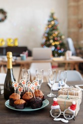 Group of tasty homemade muffins with small xmas cards on plate surrounded by bottle of champagne, Santa eyeglasses, flutes and giftboxes