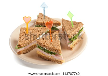 Group of tea sandwiches with  cheese, ham and lettuce on a plate isolated on white background