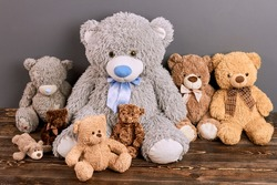 Group of teddy bears. Soft toys on brown wood. Online toy shop.