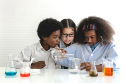 Group of teenage cute little students child learning research and doing a chemical experiment while making analyzing and mixing liquid in test tube at experiment laboratory class at school.Education