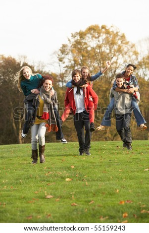 Group Of Teenage Friends Having Piggyback Rides In Autumn Landscape