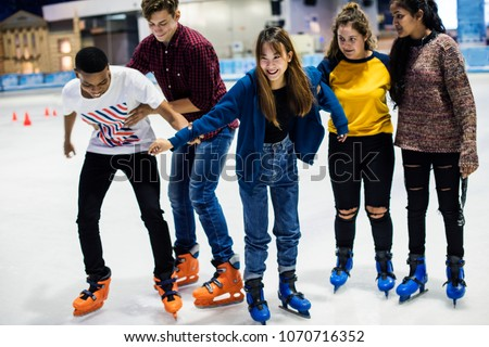 Group of teenage friends ice skating on an ice rink #1070716352