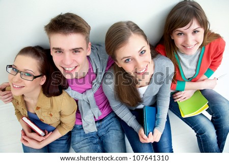 group of teenage friends look up at the camera with bright smiles
