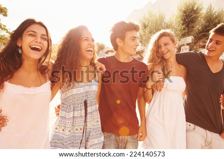 Group Of Teenage Friends Walking Along Street