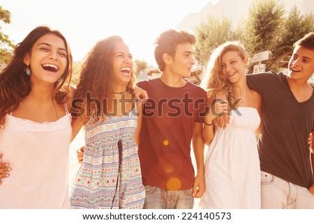 Group Of Teenage Friends Walking Along Street